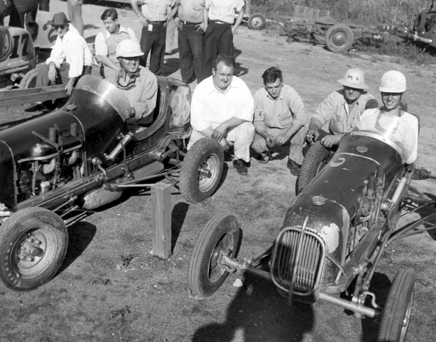 "At the Hammond, Indiana Speedway 5/8th's mile track are two Nichels midgets. The car on the left is the #25 driven by Mike O'Halloran and on the right is Teddy Duncan in the #2. Both drivers would eventually be elected to the National Midget Racing Hall of Fame. Kneeling between the Nichels cars are from left: Dale ""Tiny' Worley, Ray Nichels and Rudy Nichels – Nichels Engineering Archives"