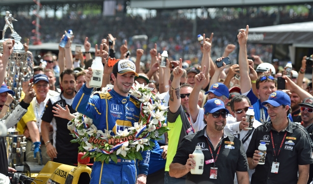 Alexander Rossi toasts with ice cold milk in Victory Circle following his win in the 100th -- IMS Image by Eric Anderson