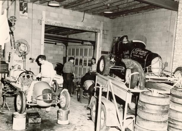 Rudy Nichels shop at the corner of Cline Avenue and Ridge Road in Highland, Indiana in 1947. Working on the two Nichels owned midgets in the front of the garage is 24 year old Ray Nichels. In the back on the right in the white tee shirt is Ronney Householder, who at the time was one of the most respected drivers in racing. He went on to manage Chrysler Corporation's racing operations from 1955 thru 1972 – Nichels Engineering Archives