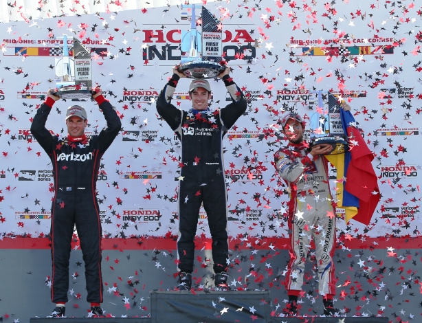 The podium of Simon Pagenaud, Will Power, and Carlos Munoz hoist their trophies in Victory Circle following the Honda Indy 200 at Mid-Ohio -- IndyCar Image by Chris Jones